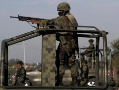 Mexican army soldiers stand guard at a check point on the outskirts of Culiacan, northern Mexico.