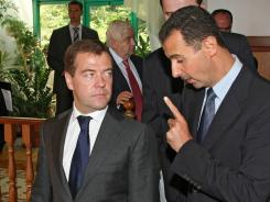 Russian President Dmitry Medvedev, left, speaks with Syrian President Bashar al-Assad in Sochi, Russia. Russia on Wednesday warned that passing a U.N. resolution on Syria would pave the way toward civil war in the country.