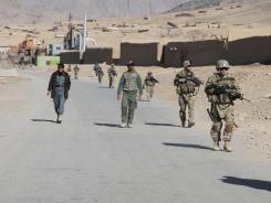 Afghan policemen walk with U.S. soldiers Jan. 7 in Kandahar. U.S. defense officials say Afghans attacked American troops for personal reasons in most cases.