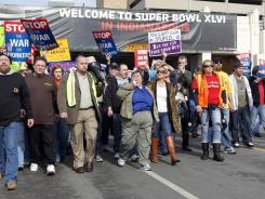 Indiana AFL-CIO President Nancy Gayott, blue shirt center, leads union protesters on a march through the Super Bowl Village in Indianapolis after the state Senate voted to pass a right-to-work bill Wednesday. Gov. Mitch Daniels signed the bill later in the day.
