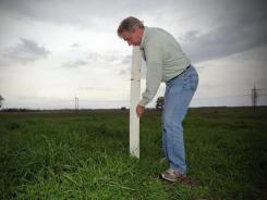 Chris Brantley, of the Army Corps of Engineers, stakes markers at the Bonnet Carre Spillway site, where about 150 slaves were buried in the 19th century.