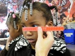 Deshawntae Clayton, 3, is measured for new glasses after a screening through Head Start.