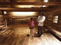 Robert Cooley teaches his daughter Cree Rayford, 7, about a slave house Dec. 2.
