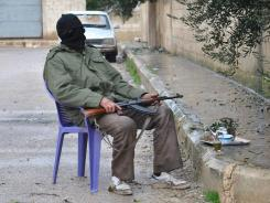 A rebel guards an alley in Syria's Homs province on Wednesday. A United Nations resolution aims to stop the bloodshed in the country.
