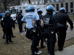 A member of Occupy DC is removed by U.S. Park Police on Saturday. Police moved in before dawn to enforce no-camping rules.