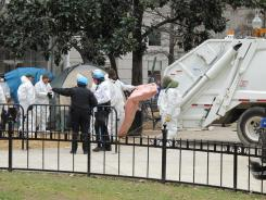 U.S. Park Police and sanitation workers throw camping materials into a garbage truck Saturday at the Occupy D.C. encampment.