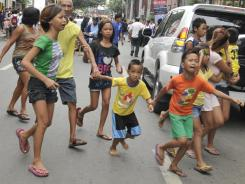 Residents run to safety after a 6.9-earthquake hit Cebu City in the Philippines on Monday.