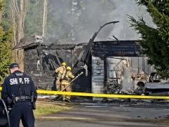 A Pierce County Sheriff's deputy and Graham Firefighters work around the smoldering remains of a house near Fredrickson, Wash. on Sunday, where the bodies of Josh Powell and his two sons were found.