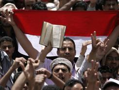 May revolutionaries: Yemeni anti-government protesters hold up a national flag and a copy of Islam's holy book, the Quran, in Sanaa.