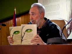 Former Cuban president Fidel Castro shows copies of his two-volume memoir on Feb. 3 at Convention Palace in Havana.