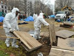 National Park Service workers remove debris from the Occupy D.C. encampment Sunday in Washington.
