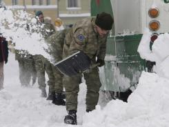 Turkish soldiers, members of the European Union Force in Bosnia-Herzegovina, shovel snow from tracks beneath a frozen tram Sunday in the Bosnian capital of Sarajevo.