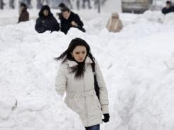 A woman walks through a snow-covered street in Sarajevo on Monday. Serbia and Bosnia closed schools.