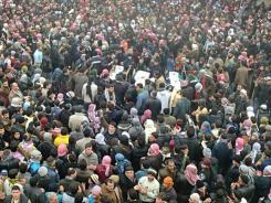 Mourners gather for a funeral procession around the bodies of people allegedly killed by Syrian government forces.