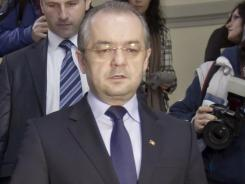 Romanian Premier Emil Boc leaves the headquarters of the ruling Democratic Liberal party in Bucharest after announcing his immediate resignation.
