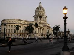 People walk past the Capitol building in Havana on Tuesday. The U.S. economic embargo on Cuba turned 50.