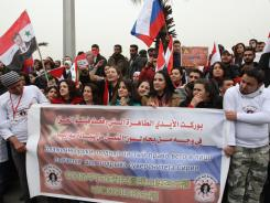 Syrian pro-government protesters hold a banner as a convoy carrying Russian Foreign Minister Sergei Lavrov heads toward the presidential palace in Damascus on Tuesday.