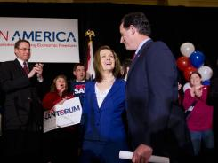 Rick Santorum takes the stage with his wife, Karen, on Tuesday night to address supporters in St. Charles, Mo.