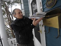 David Gerber retrieves the mail at his Buffalo home Thursday. The volume of stamped letters went down last year for the sixth straight year.