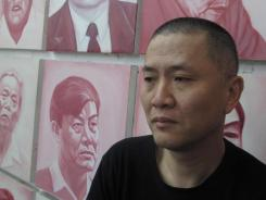 Artist and filmmaker Zhang Bingjian stands before cheap portraits he commissioned of corrupt Chinese officials in his Beijing studio.
