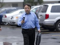 Emilio Palacio checks his phone as he arrives at the immigration center in Miami for a hearing on Wednesday.