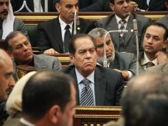 "Egypt's Prime Minister Kamal el-Ganzouri, center, insists authorities ""can't back down or won't change course because of some aid."""