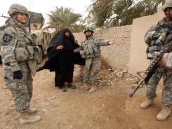A U.S. female soldier shows the way to an Iraqi woman, as she arrives at an improvised clinic set up by the U.S. military, at a school on the al-Abara neighborhood of Baquba.