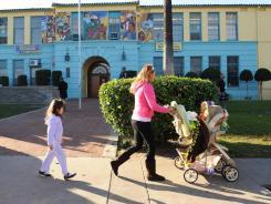 Miriam Ruiz walks with her children past Miramonte Elementary School in Los Angeles on Wednesday morning.