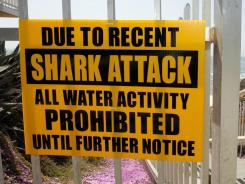 A sign prohibiting water activity above Tide Beach after a shark attack in Solana Beach, Calif., in 2008.