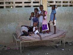Children stand on a cot Wednesday at a camp set up for people displaced by the 2010 earthquake in Port-au-Prince, Haiti.