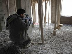 A rebel peers through the scope on his weapon Thursday in Idlib, Syria. Syrian forces fired mortars and rockets Thursday in the rebellious city of Homs.
