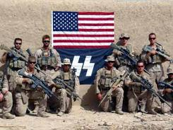 "This September 2010 photo shows members of Marine Charlie Company, 1st Reconnaissance Battalion sniper team posing in front of a flag with a logo resembling that of notorious Nazi ""SS."""