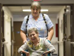 Melanie Ephraim pushes Jeannette Stenger, 80, to a crafts class at Christian Care Nursing Center in Phoenix on Wednesday.