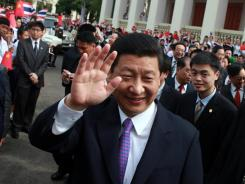 Xi Jinping waves to Thai students during a visit to Chulalongkorn University in Bangkok on Dec. 24. Xi is set to take over from President Hu Jintao.