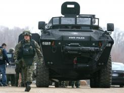 A law enforcement official walks out of an armored vehicle tank in a staging area in Hillsdale County, Mich., during a search for a fugitive who is part of a Christian militia group on March 29, 2010.