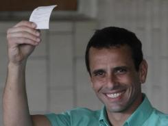 Henrique Capriles holds up his ballot at a polling station in Caracas, Venezuela, on Sunday.
