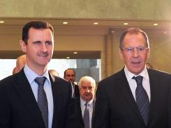 Syrian President Bashar Assad, left, stands with Russian Foreign Minister Sergey Lavrov last week. On Sunday the White House said it is only a matter of time until Assad's government collapses.