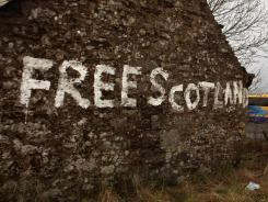 Graffiti stating 'Free Scotland' is written on the gable end wall of a cottage in Bannockburn, Scotland.