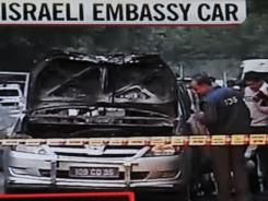 In this television frame grab taken from NDTV, investigators are seen gathered at the site where an Israeli embassy car exploded Monday in New Delhi.