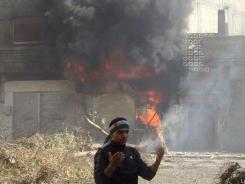 A protester reacts in front of flames that rise from a shop damaged Sunday by Syrian government forces' shelling in Homs.