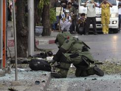 A Thai Explosive Ordnance Disposal official examines a backpack left at an explosion site by a suspected bomber in Bangkok, Thailand.