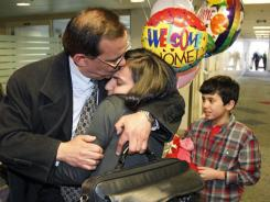 Jamal Tarhuni hugs his daughter Lena, while his son Rasheed looks on after his arrival at Portland International Airport on Tuesday.