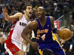Toronto Raptors guard Jose Calderon (left) battles with Los Angeles Lakers guard Kobe Bryant in Toronto on Feb. 12.