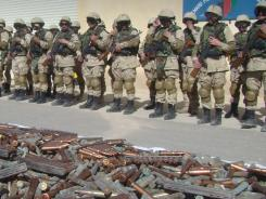 Afghan security forces stand near confiscated arms and ammunition during a news event Tuesday in Lashkar Gah, Afghanistan.