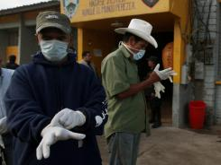 Inmates who survived a deadly prison fire put on gloves before cleaning early Thursday within the prison perimeter in Comayagua, Honduras.