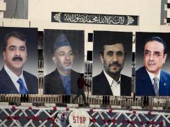 Pictures of summit leaders are displayed Thursday in Islamabad, Pakistan. From left: Pakistan's Prime Minister Yousaf Raza Gilani, Afghan President Hamid Karzai, Iranian President Mahmoud Ahmedinejad and Pakistan's President Asif Ali Zardari.