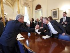 Senate Finance Committee Chairman Sen. Max Baucus, D-Mont., left, reaches out to Rep. Fred Upton, R-Mich., on Capitol Hill on Thursday to celebrate as the bipartisan House and Senate conferees on the payroll tax cut extension signed a compromise agreement.