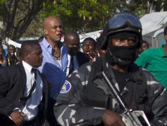 Haiti's President Michel Martelly, second from left, jogs around the University of Haiti protected by bodyguards in Port-au-Prince, on Friday.