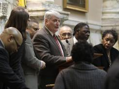 Maryland Speaker of the House of Delegates Michael Busch, center, speaks with party leaders before calling a recess in Annapolis, Md. on Friday.