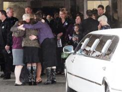 Chuck Cox, center, hugs family and mourners after the casket bearing his grandchildren, Charlie and Braden Powell, was placed in a hearse on February 11 at Tacoma, Wash.